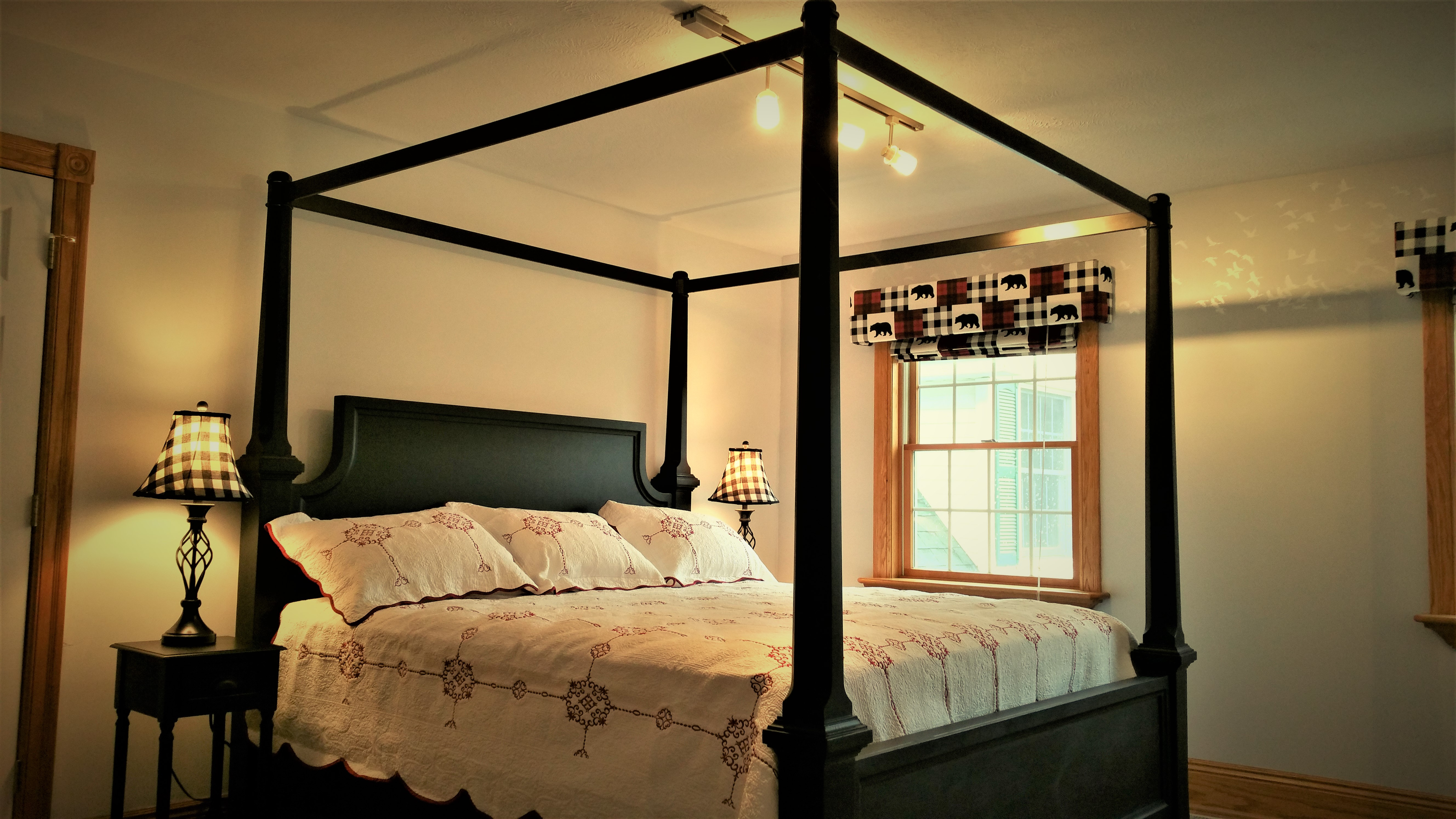 Four poster king bed with a window and lights next  to the bed